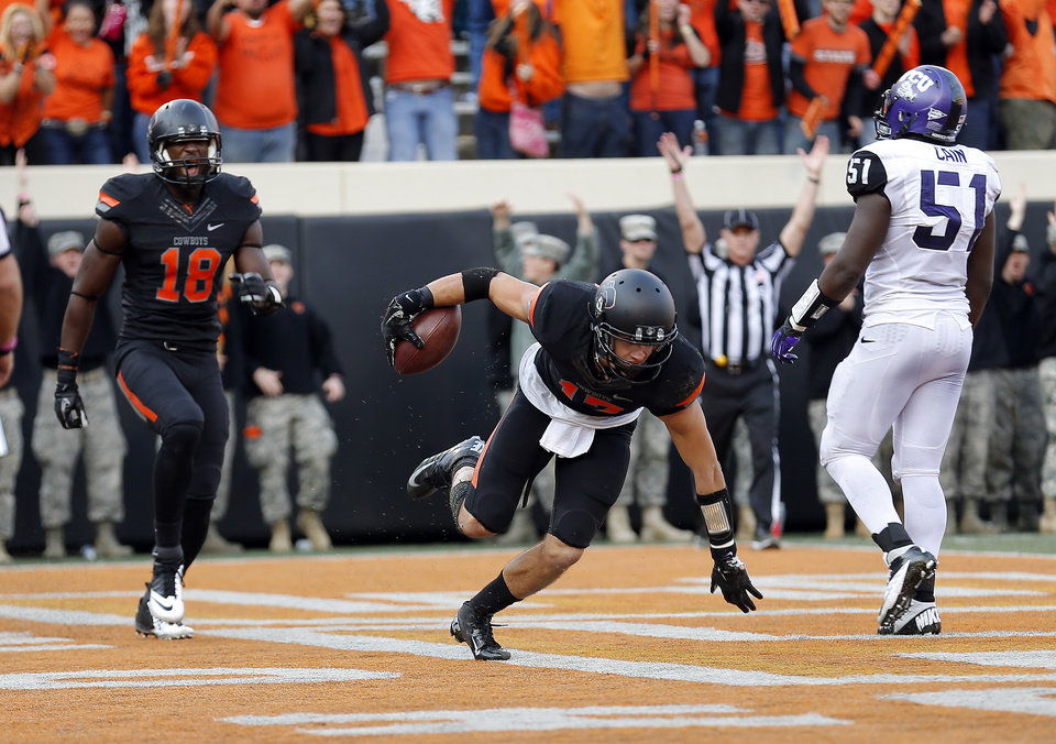 Photo - Oklahoma State's Charlie Moore (17) celebrates his touchdown with Blake Jackson (18) in front of TCU's Kenny Cain (51) during a college football game between Oklahoma State University (OSU) and Texas Christian University (TCU) at Boone Pickens Stadium in Stillwater, Okla., Saturday, Oct. 27, 2012. Photo by Sarah Phipps, The Oklahoman