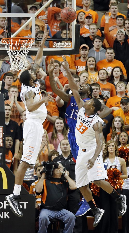 Photo - Oklahoma State 's Michael Cobbins (20) and Marcus Smart (33) defend on Kansas' Elijah Johnson (15) during the college basketball game between the Oklahoma State University Cowboys (OSU) and the University of Kanas Jayhawks (KU) at Gallagher-Iba Arena on Wednesday, Feb. 20, 2013, in Stillwater, Okla. Photo by Chris Landsberger, The Oklahoman