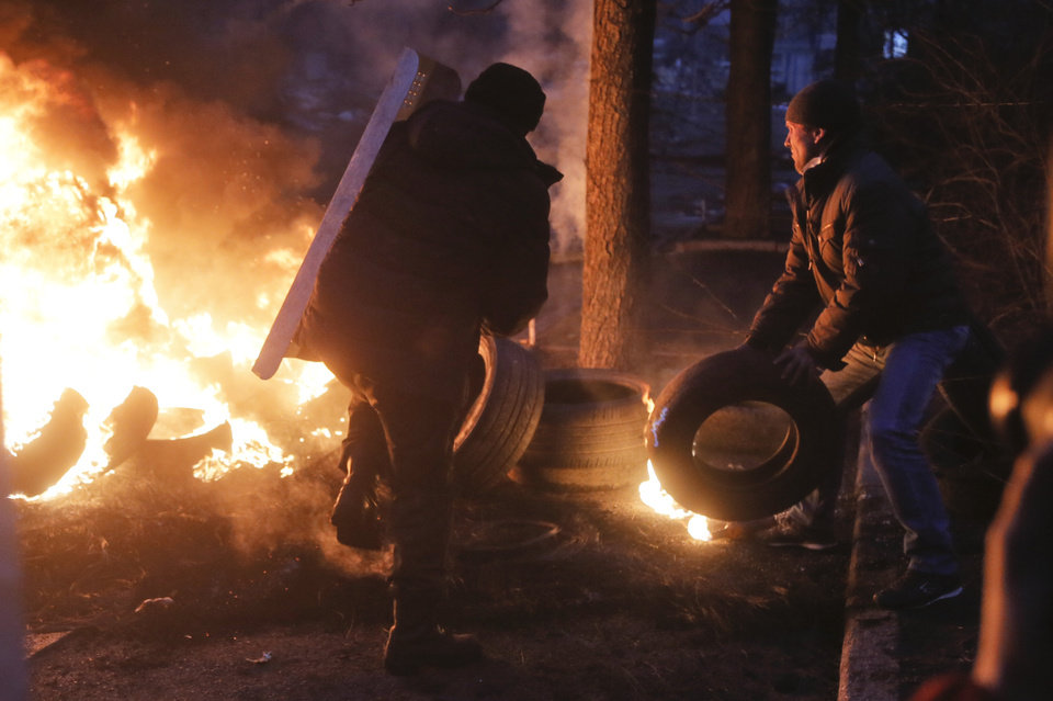 Photo - Activists burn tyres at barricades close to Independence Square, the epicenter of the country's current unrest, in Kiev, Ukraine, Thursday, Feb. 20, 2014, as, according to the protesters, the resulting heavy black smoke does not  allow riot police snipers to aim easily at protesters. Fierce clashes between police and protesters in Ukraine's capital have shattered the brief truce Thursday and an Associated Press reporter has seen dozens of bodies laid out on the edge of the protest encampment. (AP Photo / Efrem Lukatsky)