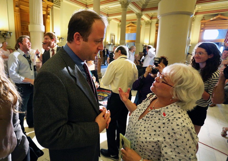 Photo - U.S. Rep. Jared Polis, D-Colo, left, speaks with Randee Webb of the organization What The Frack?! Arapahoe, following a news conference about oil and gas drilling, at the Capitol, in Denver, Monday Aug. 4, 2014. Polis joined Colo. Gov. John Hickenlooper on Monday Aug. 4 to detail what they're pitching as a compromise to prevent four initiatives that support or oppose fracking.  (AP Photo/Brennan Linsley)