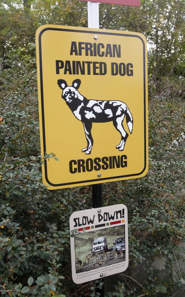 A sign to inform visitors about African Painted Dogs is seen near an observation area during a press tour near the overlook platform where a boy fell into the exhibit that was home to a pack of African painted dogs at the Pittsburgh Zoo and PPG Aquarium on Monday, Nov. 5, 2012, in Pittsburgh. Zoo officials said a young boy was killed after he fell into the exhibit and the dogs mauled him on Sunday, Nov. 4, 2012. (AP Photo/Keith Srakocic)