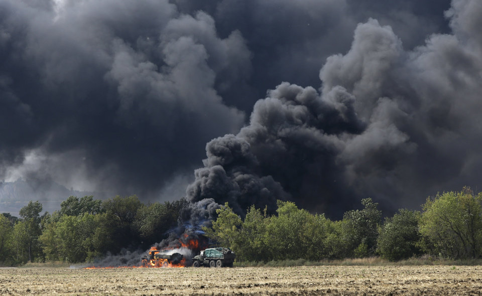 Unmarked military vehicles burn on a country road in the village of Berezove, eastern Ukraine, Thursday, Sept. 4, 2014, after a clash between pro-government troops and Russian-backed separatist militia. Separatist rebels have made major strides in their offensive against Ukrainian government forces in recent days, drawing on what Ukraine and NATO says is ample support from the Russian military. (AP Photo/Sergei Grits)
