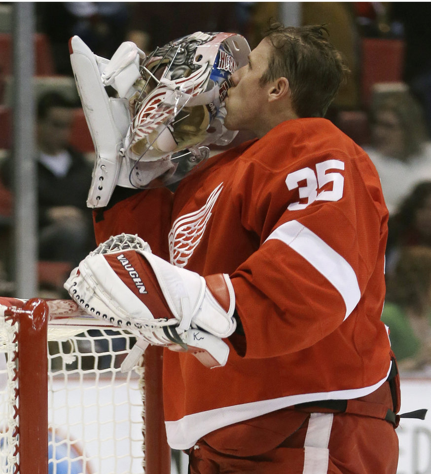 Photo - Detroit Red Wings goalie Jimmy Howard kisses his helmet during the first period of an NHL hockey game against the Washington Capitals in Detroit, Friday, Jan. 31, 2014. (AP Photo/Carlos Osorio)
