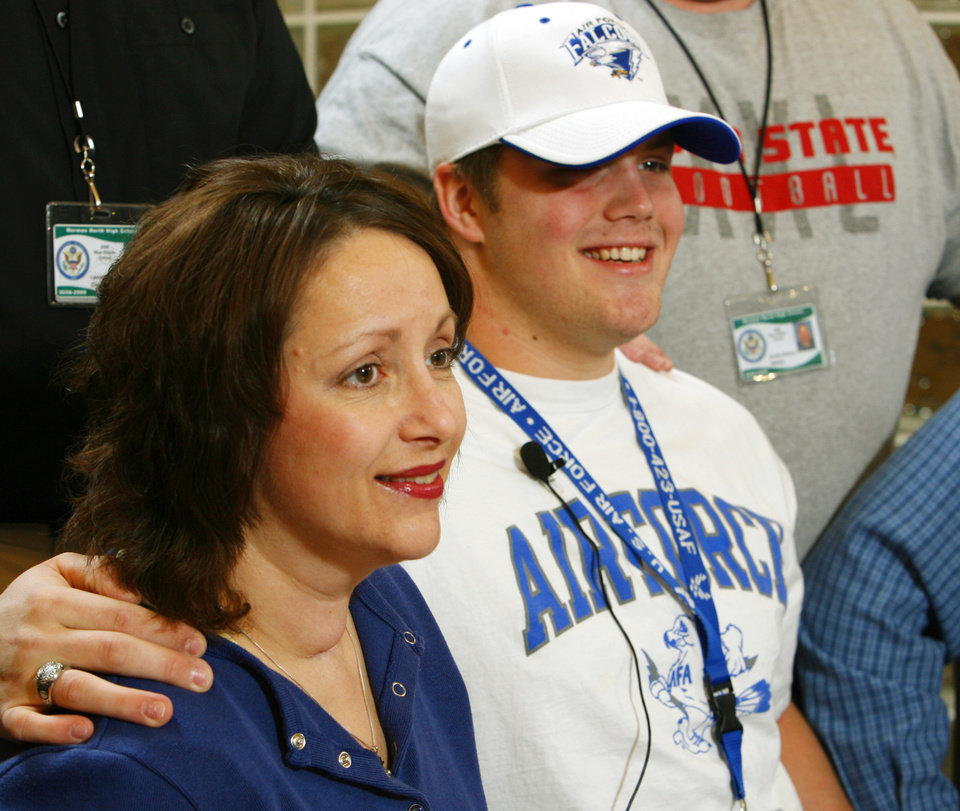 Photo - Nathan Badger puts his arm around his mother Denise after signing a letter of intent to play college football at Norman North High School in  Norman, Okla. on Wednesday, Feb. 4, 2009.    Photo by Steve Sisney, The Oklahoman
