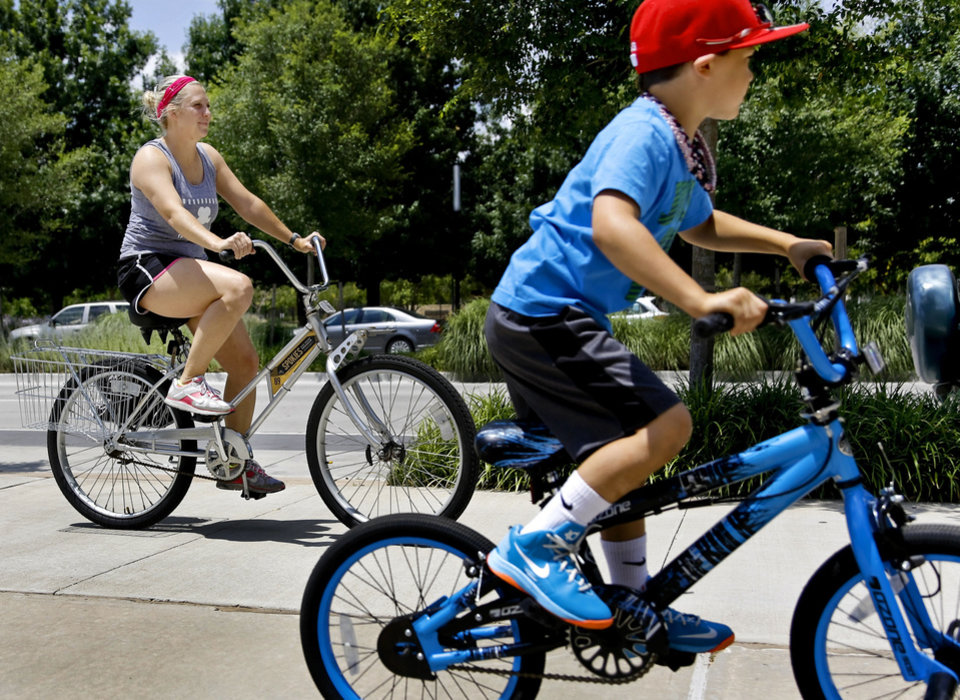 Photo - Lara Vetoyanis rides a Spokies bike share rental bike in downtown with Reid Smith, 6, near the Cox Convention Center on Monday, July 1, 2013 in Oklahoma City, Okla.      Photo by Chris Landsberger, The Oklahoman