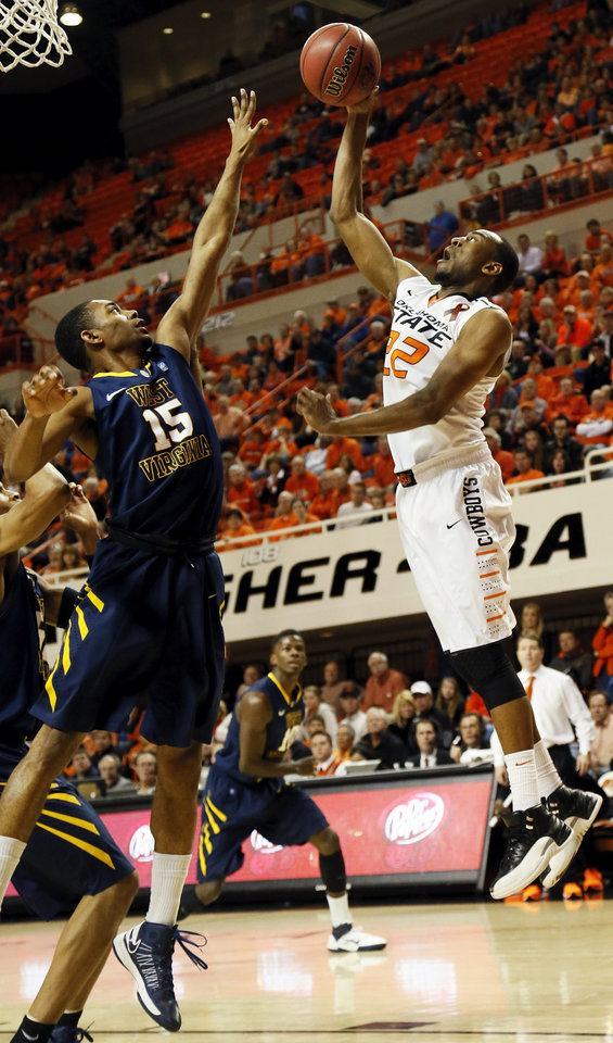Oklahoma State's Markel Brown (22) takes a shot against West Virginia's Terry Henderson (15) during an NCAA men's basketball game between Oklahoma State University (OSU) and West Virginia at Gallagher-Iba Arena in Stillwater, Okla., Saturday, Jan. 26, 2013. Oklahoma State won, 80-66. Photo by Nate Billings, The Oklahoman
