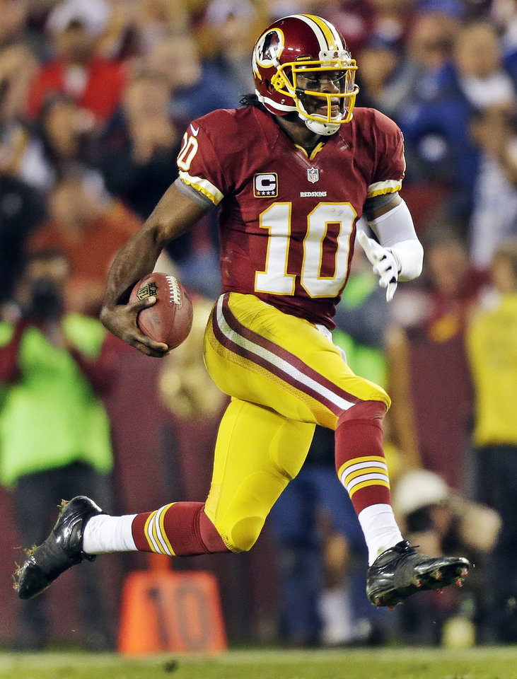 Washington Redskins quarterback Robert Griffin III scrambles with the ball during the second half of an NFL football game against the New York Giants in Landover, Md., Monday, Dec. 3, 2012. (AP Photo/Evan Vucci)