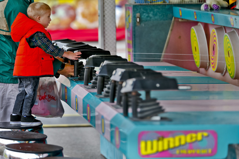 Photo - Cooper Whitworth, 3, of Oklahoma City, plays a game on the midway at the Oklahoma State Fair at State Fair Park on Friday, Sept. 14, 2012, in Oklahoma City, Oklahoma.  Photo by Chris Landsberger, The Oklahoman