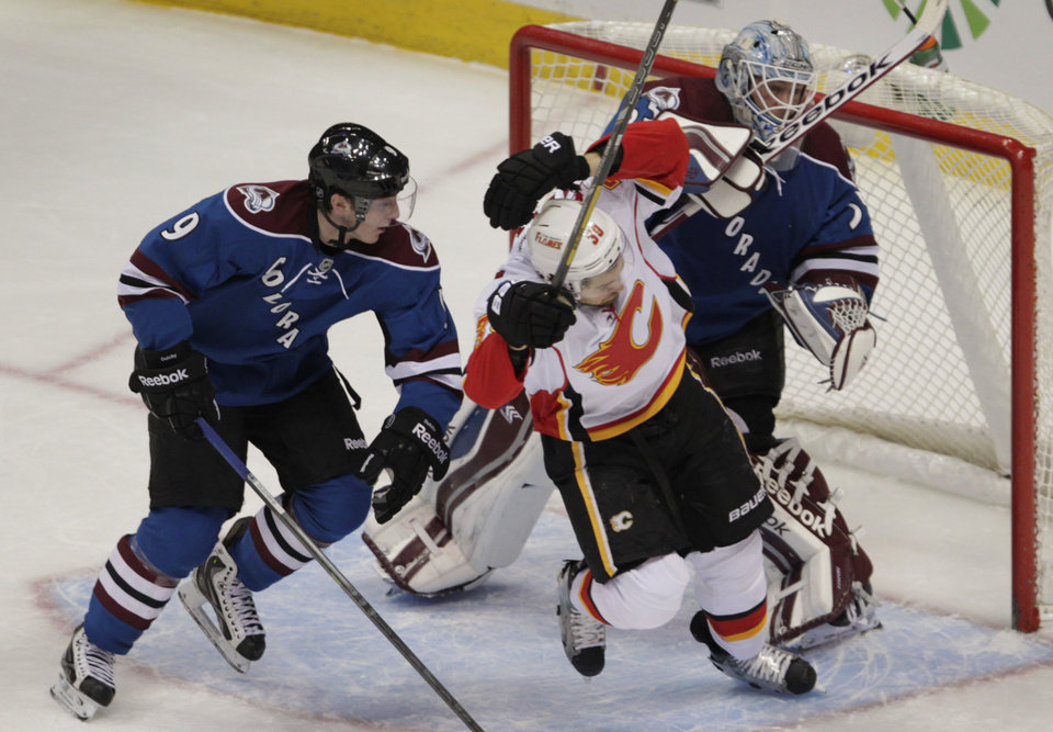 Photo - Colorado Avalanche goalie Jean-Sebastien Giguere (35) pushes Calgary Flames left wing T.J. Galiardi (39) as Avalanche center Matt Duchene (9) defends in the first period of an NHL game in Denver on Monday, Jan. 6, 2014. (AP Photo/Joe Mahoney)