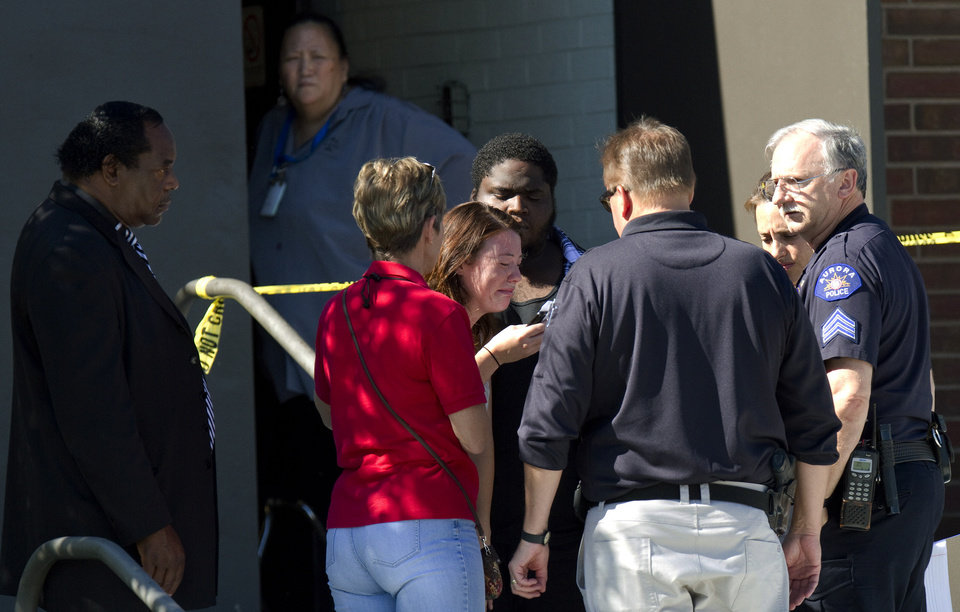 Photo - A woman overcome with emotion is sounded by councilors, police and clergy outside Gateway High School where witnesses are being interviewed by authorities Friday, July 20, 2012. A  gunman wearing a gas mask set off an unknown gas and fired into the crowded movie theater killing 12 people and injuring dozens, authorities said.  The suspect is identified as 24-year-old James Holmes. (AP Photo/Barry Gutierrez) ORG XMIT: COBG120