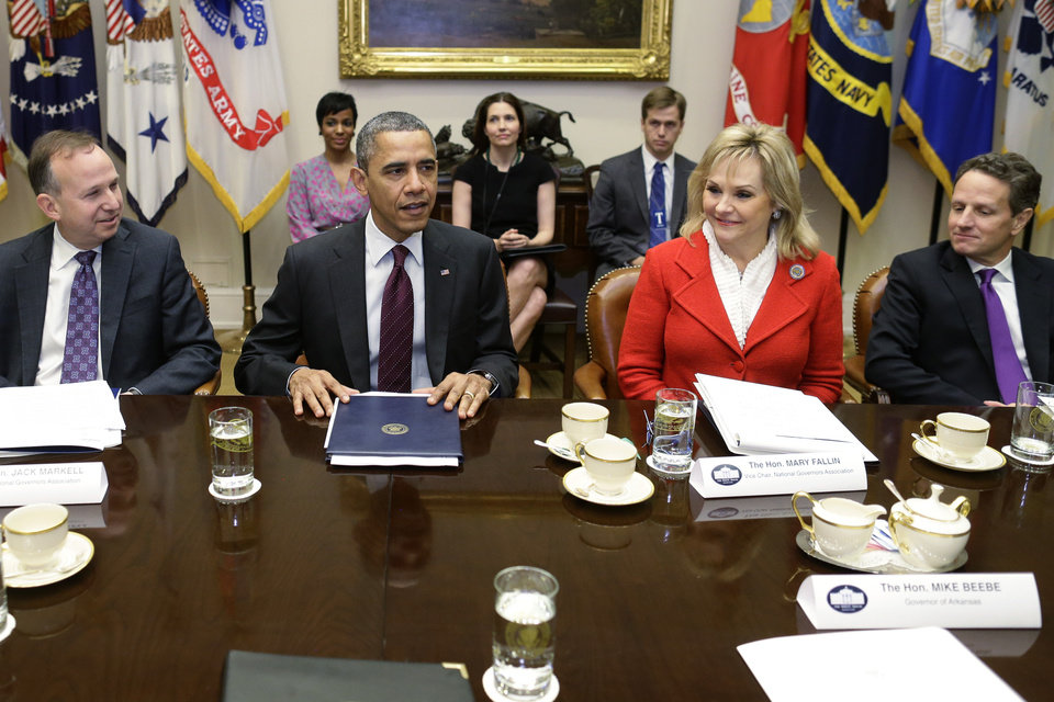 Photo - President Barack Obama, flanked by National Governors Association (NGA) Chairman, Delaware Gov. Jack Markell, left, and NGA Vice Chair, Oklahoma Gov. Mary Fallin, meets with the NGA executive committee regarding the fiscal cliff, Tuesday, Dec. 4, 2012, in the Roosevelt Room at the White House in Washington. Treasury Secretary Tim Geithner is at right. (AP Photo/Charles Dharapak)