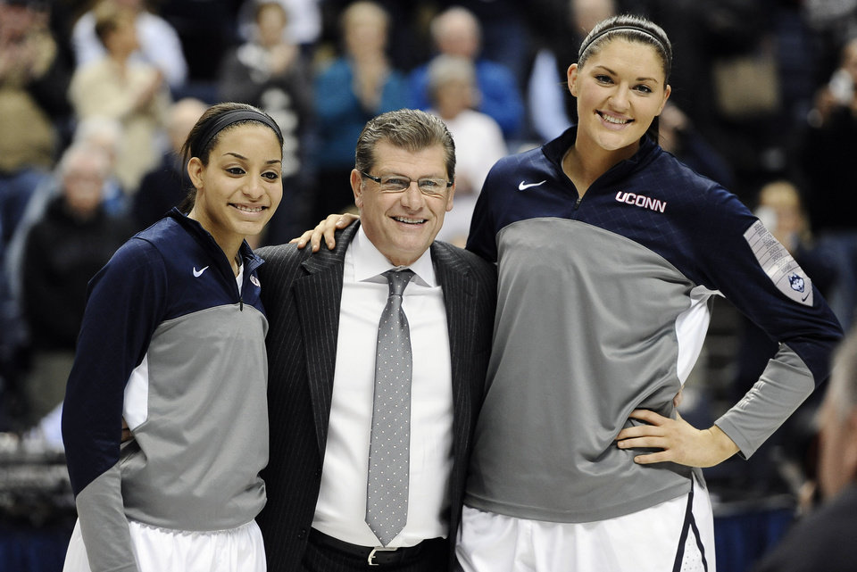Photo - Connecticut's Bria Hartley, left, and Stefanie Dolson, right, stand with head coach Geno Auriemma, center, as they are honored at senior night before an NCAA college basketball game against Rutgers, Saturday, March 1, 2014, in Storrs, Conn. (AP Photo/Jessica Hill)