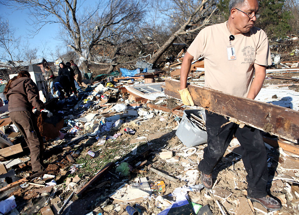 Chickasaw Nation employee Marcus Wilmond, helps clean up Shirley Mose's home following deadly storms around Lone Grove, Okla., Feb. 11, 2009. By John Clanton, The Oklahoman
