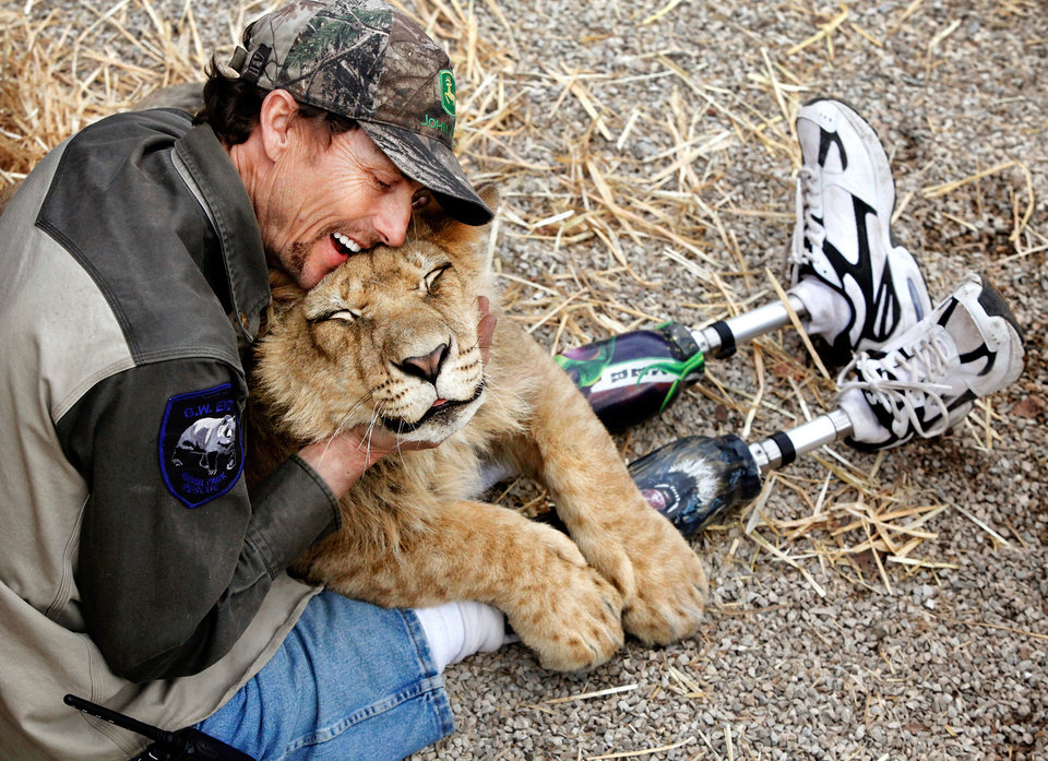 John Reinke, park manager at the G.W. Exotic Animal Park, hugs 'Bonedigger' an ailing lion that Reinke is trying to nurse back to health in a pen next to Reinke's house in the park, Wednesday, Jan. 13, 2010.  Photo by Jim Beckel, The Oklahoman