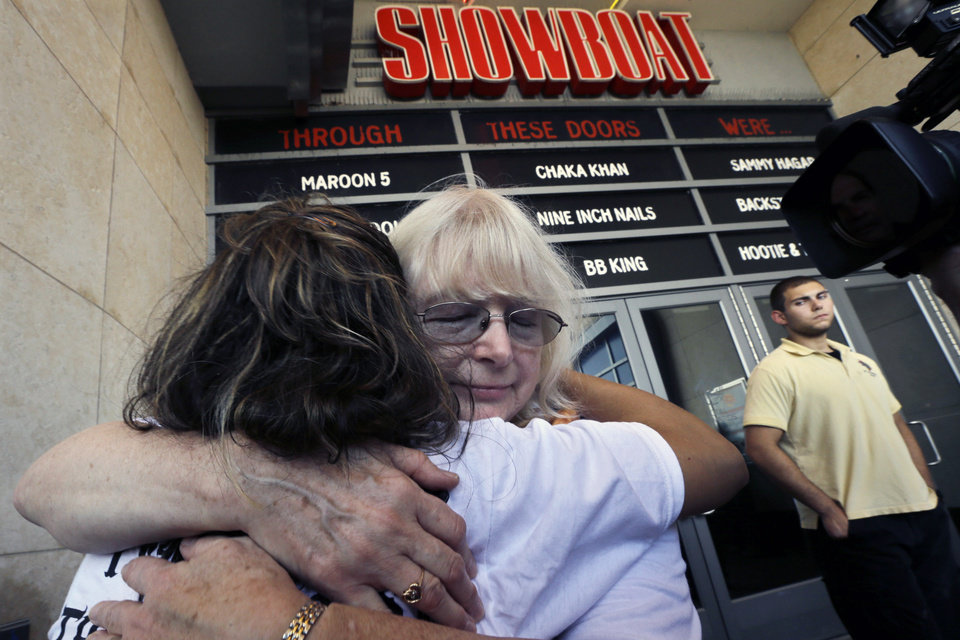 Photo - Long time employees Denise Miller, facing camera, 24 years, and Gloria Panameno, 27 years, hug as they leave the closing Showboat Casino Hotel at four-in-the-afternoon Sunday, Aug. 31, 2014, in Atlantic City, N.J. The Mardi Gras-themed casino is shutting down at 4 p.m. Sunday after 27 years on the Boardwalk. Owner Caesars Entertainment is closing the still-profitable Showboat to reduce the number of casinos in Atlantic City, which has been struggling with plunging revenue and increased competition. (AP Photo/Mel Evans)