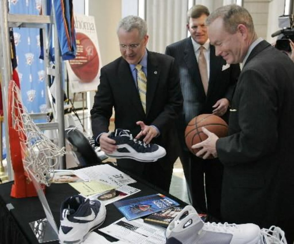 Oklahoma Gov. Brad Henry, left, and Oklahoma City Mayor Mick Cornett, right, look over several items donated by the Oklahoma City Thunder to the Oklahoma History Center in Oklahoma City, Thursday. At center is Thunder Chairman Clay  Bennett. Henry who holds a Russell Westbrook shoe.  Cornett holds an official game ball from the final home game - a victory over the Charlotte Bobcats on April 10. (AP Photo)