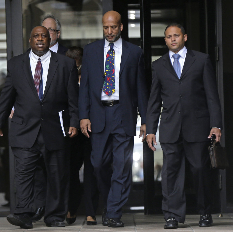 Photo - Former New Orleans Mayor Ray Nagin, center, leaves federal court after being sentenced in New Orleans, Wednesday, July 9, 2014.  Nagin was sentenced Wednesday to 10 years in prison for bribery, money laundering and other corruption that spanned his two terms as mayor, including the chaotic years after Hurricane Katrina hit in 2005. He was convicted Feb. 12 of accepting hundreds of thousands of dollars from businessmen who wanted work from the city or Nagin's support for various projects. The bribes came in the form of money, free vacations and truckloads of free granite for his family business. (AP Photo/Gerald Herbert)