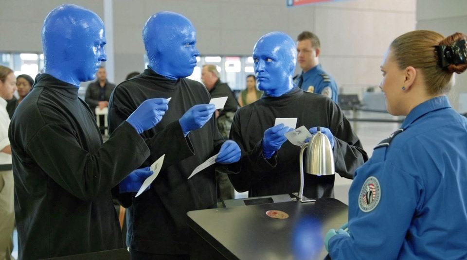 Photo - In this frame from video provided by R&R Partners and released in May 2014, Las Vegas performers Blue Man Group present documents to a Transportation Security Administration official in one of eight funny videos that play at security checkpoints at Las Vegas' McCarran International Airport. Tourism officials released the humorous new videos illustrating TSA policies as travelers wait for screenings. Other videos feature Las Vegas comedians Carrot Top, Louie Anderson, ventriloquist Terry Fator, among others. They address TSA procedures for liquids, gels and aerosols, metals and electronics, carry-on luggage, strollers, weapons and more. (AP Photo/R&R Partners)