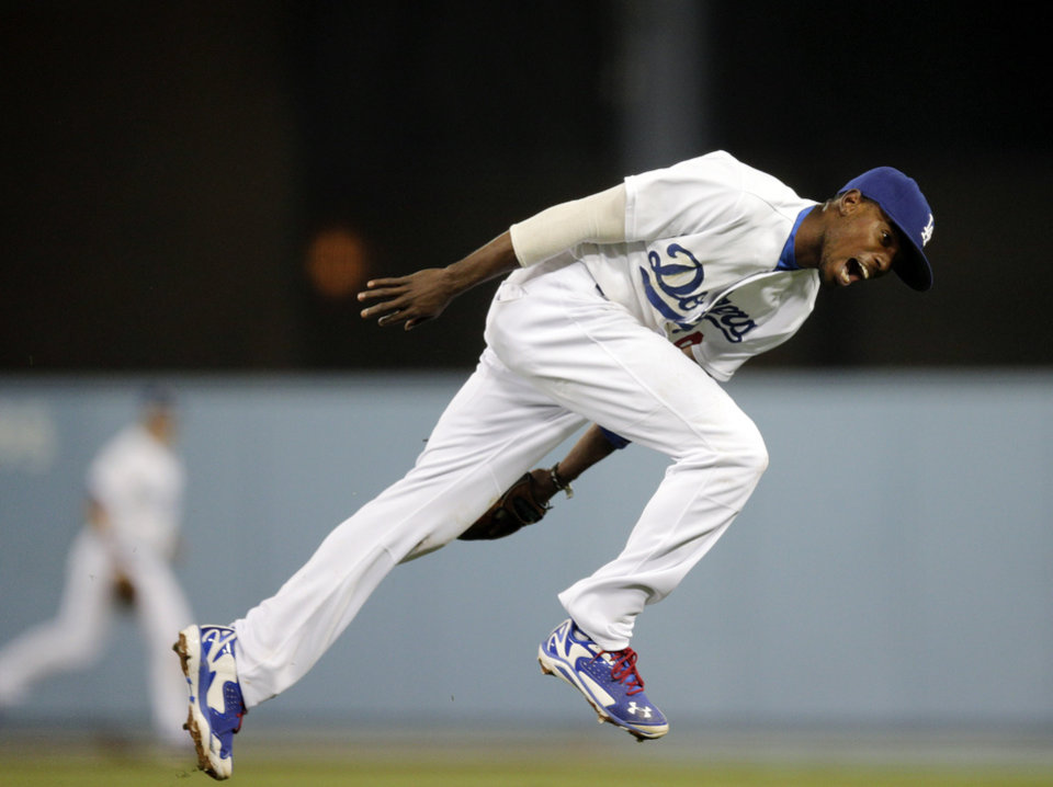 Photo - Los Angeles Dodgers second baseman Dee Gordon can't catch a single hit by Cincinnati Reds' Jay Bruce during the seventh inning of a baseball game on Tuesday, May 27, 2014, in Los Angeles. (AP Photo/Jae C. Hong)