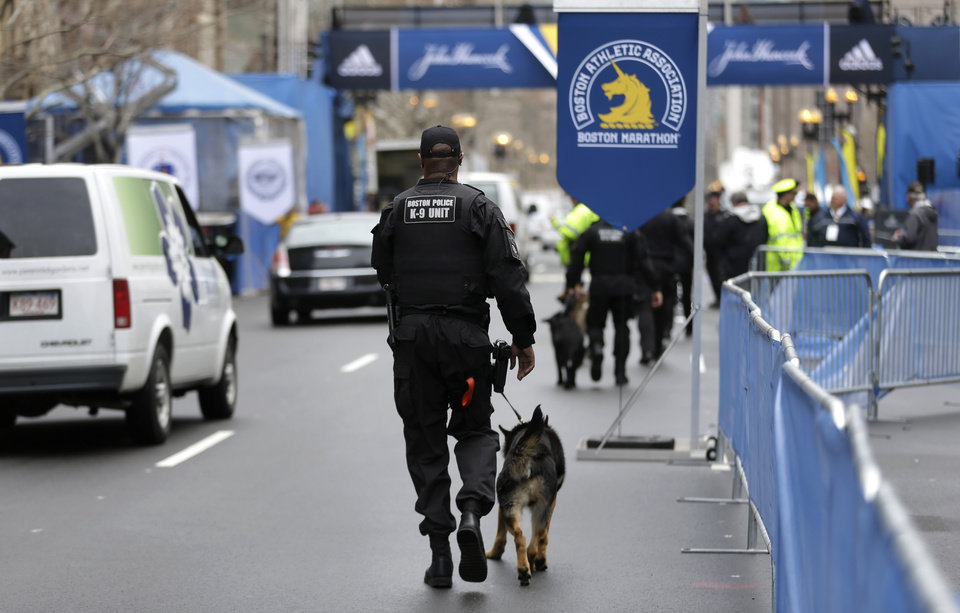 Photo - A law enforcement official patrols the area with a dog near the finish line of the Boston Marathon, Tuesday, April 15, 2014, in Boston. Vice President Joe Biden is expected to be among the dignitaries Tuesday during ceremonies to honor victims, and the first responders, doctors and nurses who helped them, following the April 15, 2013, bombings, during a tribute at the Hynes Convention Center in Boston. (AP Photo/Steven Senne)