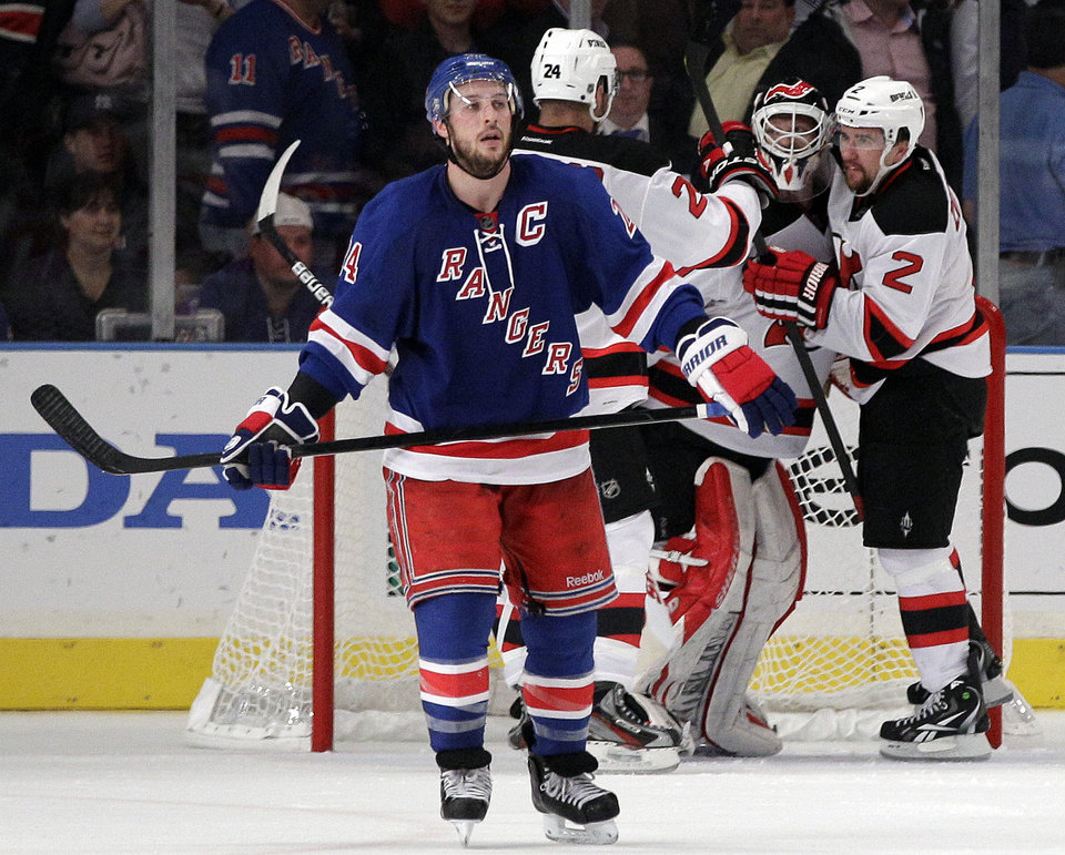 Photo -   New York Rangers' Ryan Callahan, left, skates away as New Jersey Devils goalie Martin Brodeur, center, celebrates with Marek Zidlicky, right, after Game 2 of the NHL hockey Stanley Cup Eastern Conference final playoff series, Wednesday, May 16, 2012, in New York. The Devils won 3-2. (AP Photo/Frank Franklin II)