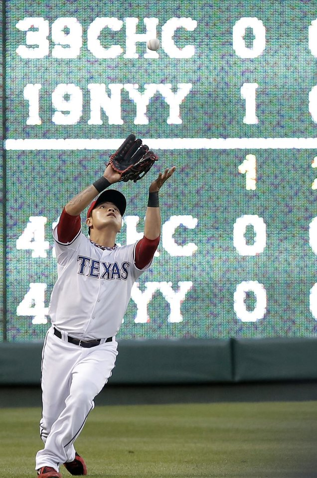 Photo - Texas Rangers left fielder Shin-Soo Choo (17) catches a fly ball hit by Seattle Mariners' Michael Saunders during the third inning of a baseball game on Wednesday, April 16, 2014, in Arlington, Texas. (AP Photo/Brandon Wade)