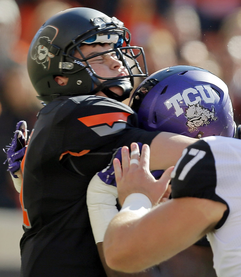 Photo - Oklahoma State's Wes Lunt (11) is pressured by TCU's Chucky Hunter (96) during a college football game between Oklahoma State University (OSU) and Texas Christian University (TCU) at Boone Pickens Stadium in Stillwater, Okla., Saturday, Oct. 27, 2012. Photo by Nate Billings, The Oklahoman