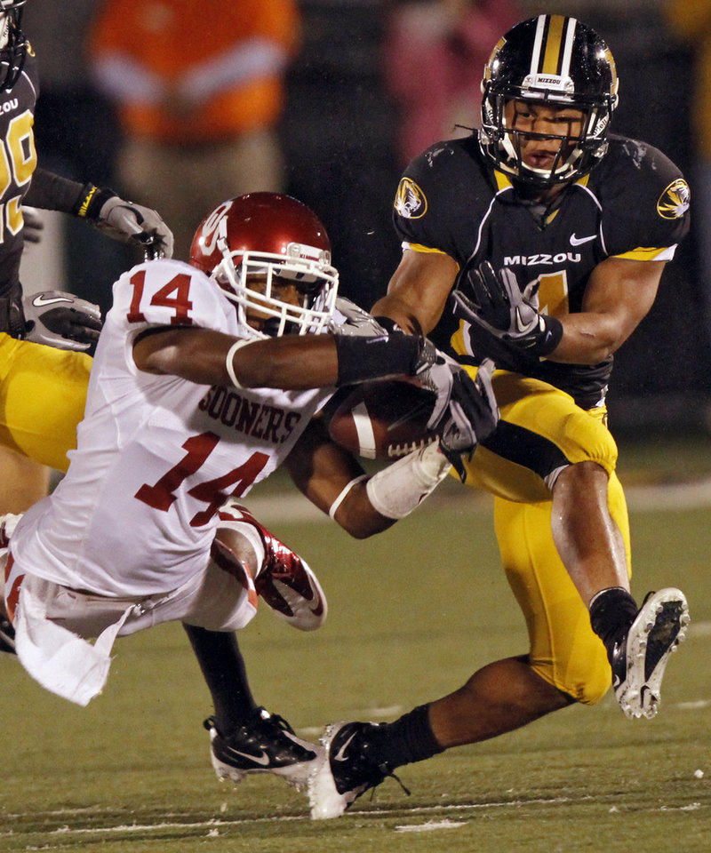 Photo - Oklahoma's Aaron Colvin (14) breaks up a pass for Missouri's Kendial Lawrence (4) during the second half of the college football game between the University of Oklahoma Sooners (OU) and the University of Missouri Tigers (MU) on Saturday, Oct. 23, 2010, in Columbia, Mo. Oklahoma lost the game 36-27. Photo by Chris Landsberger, The Oklahoman