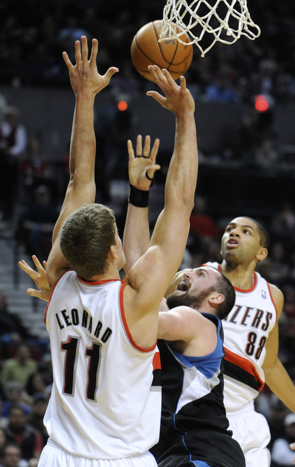 Photo -   Minnesota Timberwolves' Kevin Love shoots between Portland Trail Blazers' Meyers Leonard (11) and Nicolas Batum (88) during the first half of an NBA basketball game in Portland, Ore., Friday, Nov. 23, 2012. (AP Photo/Greg Wahl-Stephens)