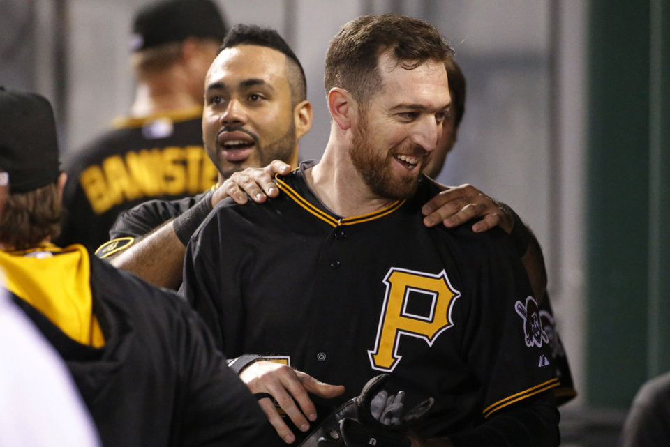 Photo - Pittsburgh Pirates' Ike Davis, right, celebrates his grand slam with teammate Pedro Alvarez in the dugout during the fourth inning of a baseball game against the Cincinnati Reds in Pittsburgh Monday, April 21, 2014. (AP Photo/Gene J. Puskar)