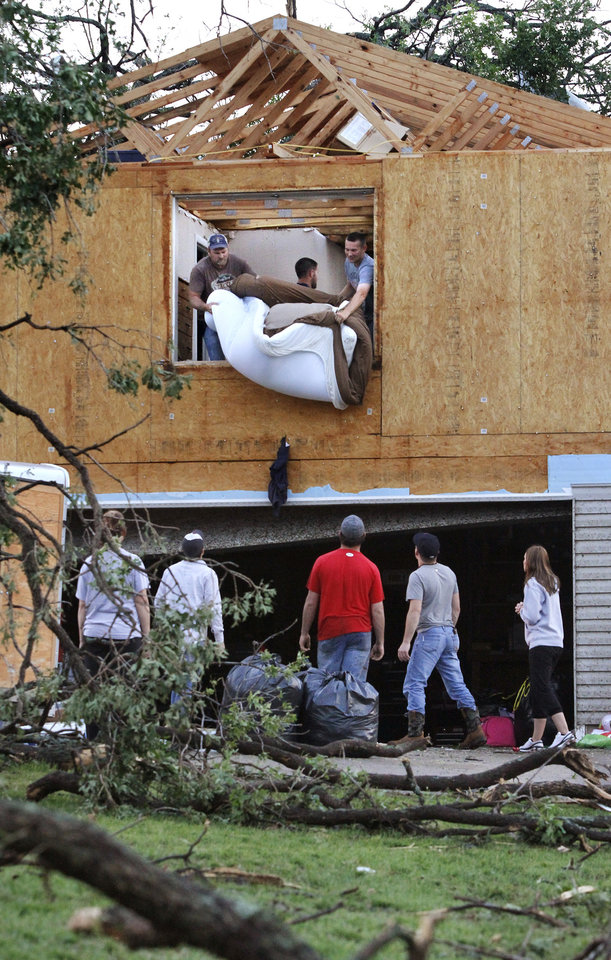 Men lower a mattress to friends from an upstairs room of this house heavily damaged in Sunday's tornado. A tornado caused extensive damage along I-40 at the junction with  US 177 on the west side of Shawnee Sunday evening,  May 19,  2013.  Photo  by Jim Beckel, The Oklahoman.