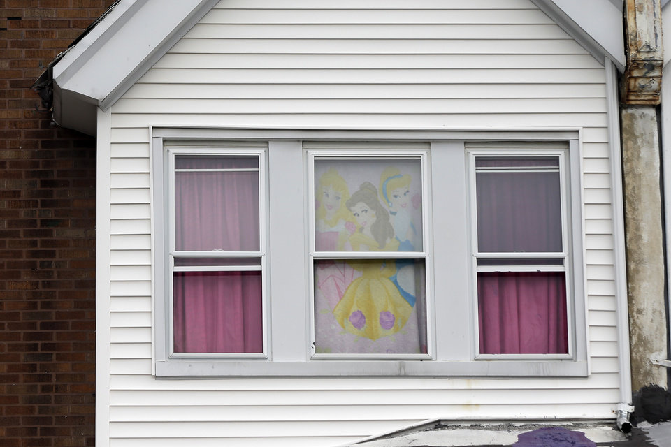 Shown is a decorated window of the home of a severely disabled 3-year-old girl who was pronounced dead at a nearby hospital, Monday, Sept. 9, 2013, in Philadelphia. Nathalyz Rivera, a twin, weighed just 11 pounds when she died and police in Philadelphia called her death a homicide. Police are searching for the girl's father, Carlos Rivera, after they said he left four other children in a relative's care and fled. (AP Photo/Matt Rourke)