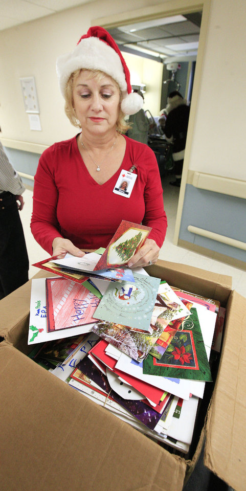 Photo - Elena LeGree, Tinker Red Cross Service to the Armed Forces coordinator, selects Christmas cards provided by the Holiday Mail for Heroes program.  Photo by Paul B. Southerland, The Oklahoman  PAUL B. SOUTHERLAND - PAUL B. SOUTHERLAND