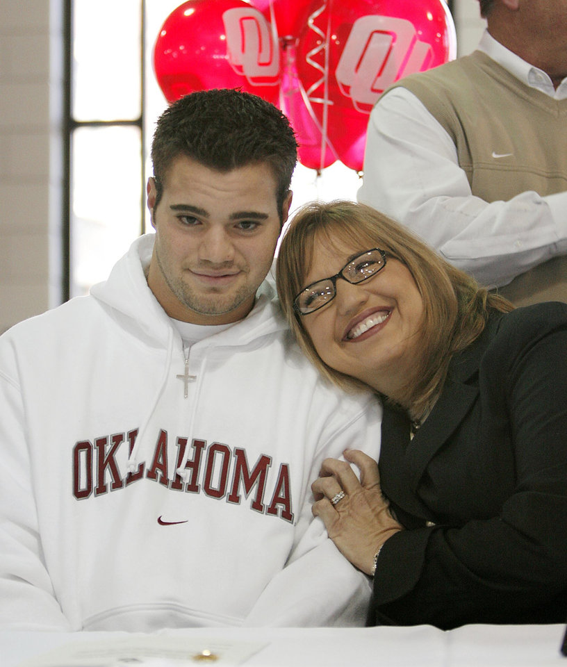 Photo - Enid's Austin Box gets a hug from his mother Gail after Box signed his letter of intent to play football with the University of Oklahoma on Wednesday, Feb. 7, 2007, in Enid, Okla.     by Chris Landsberger, The Oklahoman