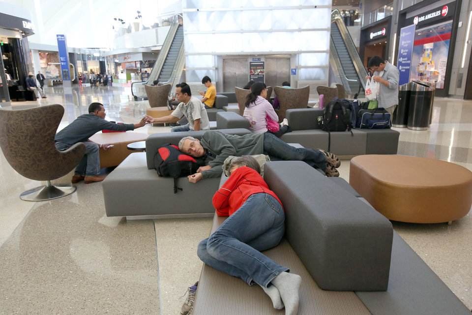 Photo - In this Monday, May 5, 2014 photo, passengers sleep on new couches in the Tom Bradley International Terminal at Los Angeles International Airport (LAX). TBIT is a completed part of improvements  at the aging airport, which is scheduled to get newly surfaced roads, upgraded restaurants with Los Angeles themes, and some terminal makeovers that will infuse more sunlight into otherwise cave-like interiors. Also in the plans are new bathrooms and, that essential for travelers, more outlets and USB ports for charging electronic devices.  (AP Photo/Nick Ut )