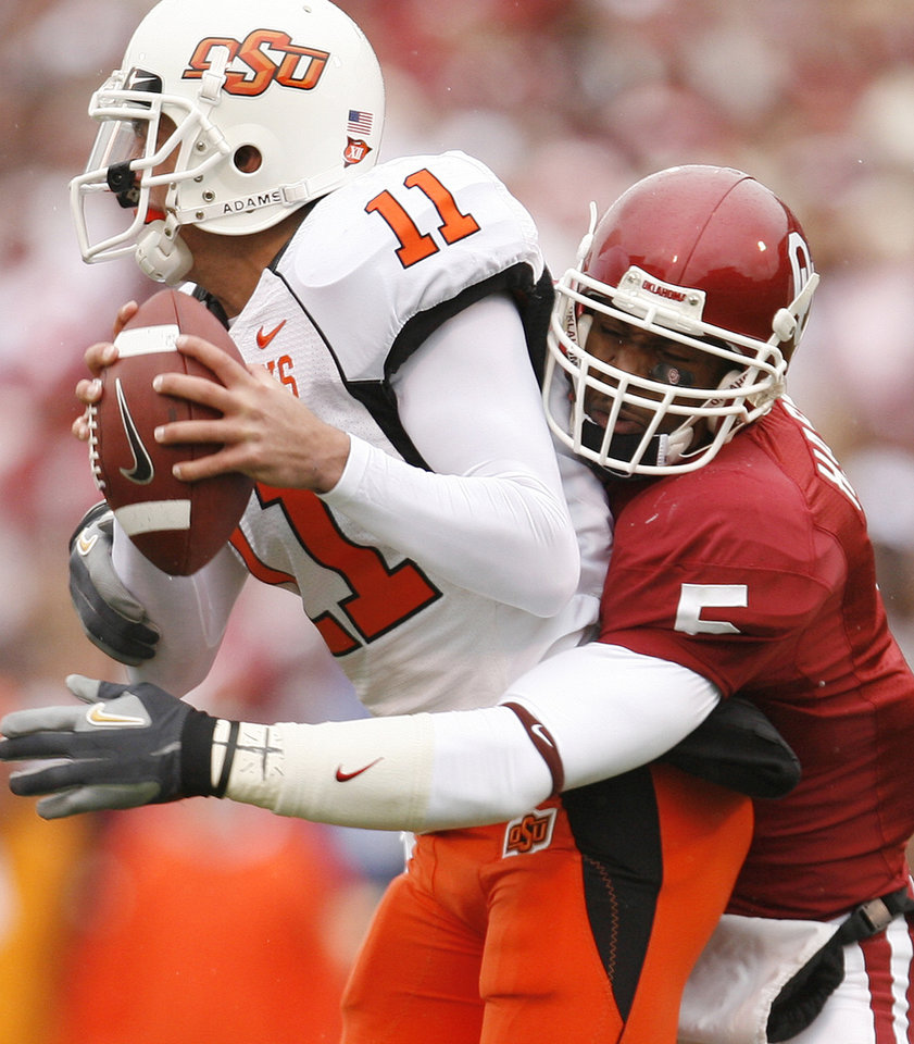 Photo - Oklahoma's Nic Harris (5) sacks Oklahoma State quarterback Zac Robinson (11) during the first half of the college football game between the University of Oklahoma Sooners (OU) and the Oklahoma State University Cowboys (OSU) at the Gaylord Family-Memorial Stadium on Saturday, Nov. 24, 2007, in Norman, Okla.  Photo By Bryan Terry, The Oklahoman