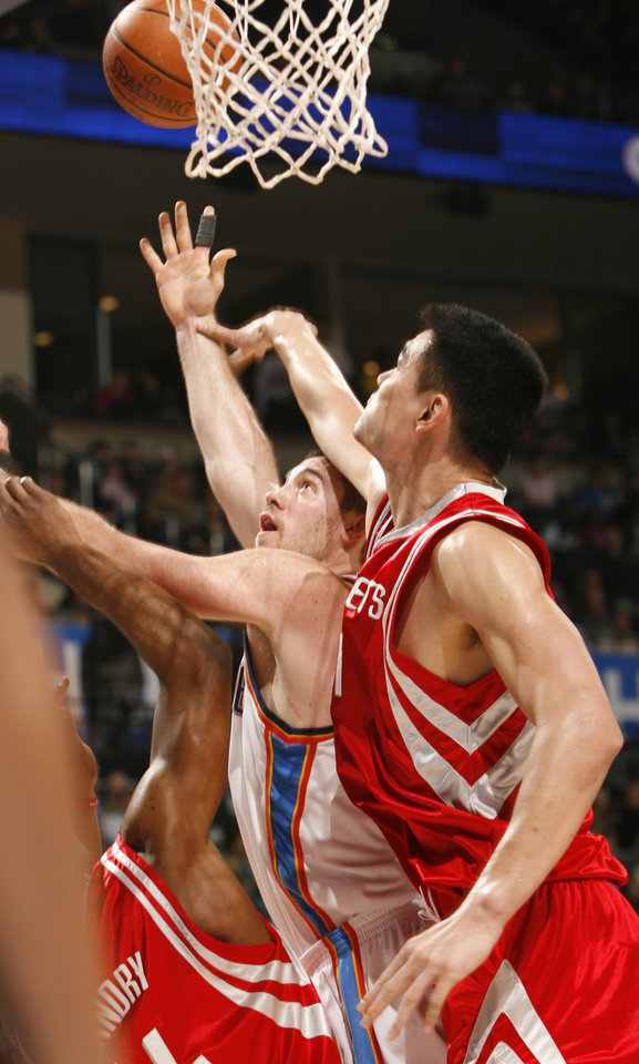 Nick Collison is sandwiched by Carl Landry and Yao Ming in the first half as the Oklahoma City Thunder plays the Houston Rockets at the Ford Center in Oklahoma City, Okla. on Friday, January 9, 2009. 
