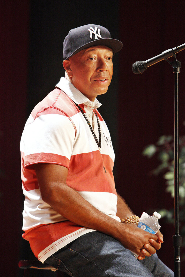 Photo - Russell Simmons, co-founder of the hip-hop label Def Jam and creator of the clothing fashion line Phat Farm, answers student questions while speaking Wednesday afternoon at John Marshall High School in northwest Oklahoma City. Simmons visited the school before speaking to business students at the University of Central Oklahoma, which paid for his visit to Oklahoma. Photo by Paul B. Southerland, The Oklahoman  PAUL B. SOUTHERLAND - THE OKLAHOMAN