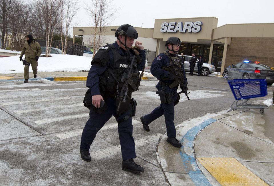 Photo - Police move in from a parking lot to the Mall in Columbia after reports of a multiple shooting, Saturday Jan. 25, 2014 Howard County, Md.  Police in Maryland say three people died Saturday in a shooting at a mall in suburban Baltimore, including the presumed gunman.  ( AP Photo/Jose Luis Magana)