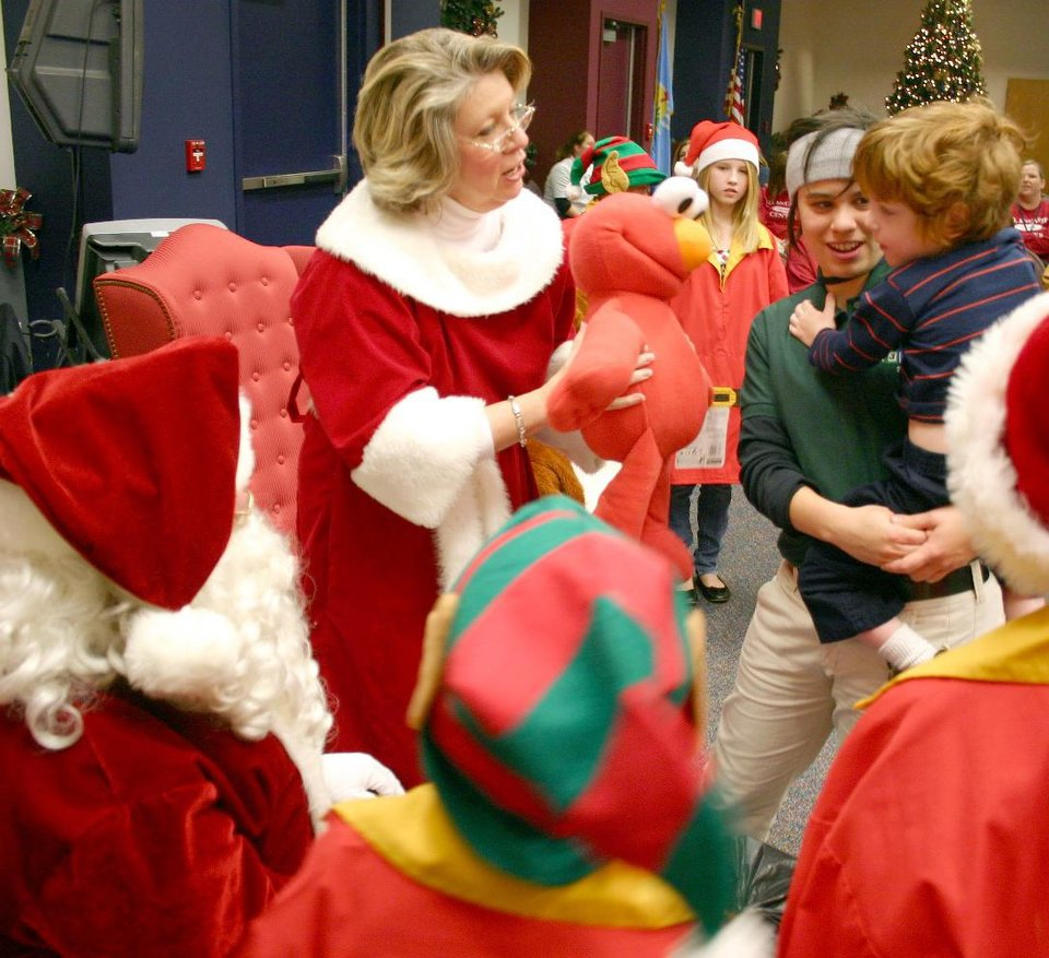Mrs. Claus offers an Elmo to an Earl…Earl Halbritter a young patient at the J. D. McCarty Center in Norman... during the Oklahoma Municipal Contractor's Association annual Christmas party for the rehab hospital's inpatients.  Holding Halbritter is Natalie Bell, McCarty Center direct care specialist. Portraying Mr. and Mrs. Santa Claus are OMCA members Don Manning and Vicki Moore.<br/><b>Community Photo By:</b> Greg Gaston<br/><b>Submitted By:</b> Greg, Norman