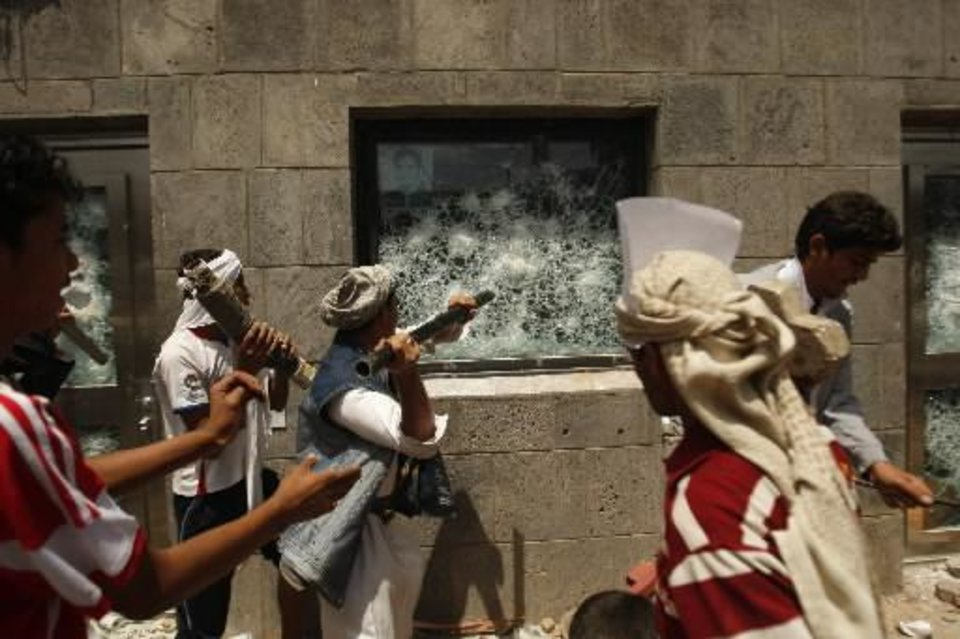 Photo - Yemeni protesters break a window of the U.S. Embassy during a protest about a film ridiculing Islam's Prophet Muhammad, in Sanaa, Yemen, Thursday, Sept. 13, 2012. Dozens of protesters gather in front of the US Embassy in Sanaa to protest against the American film
