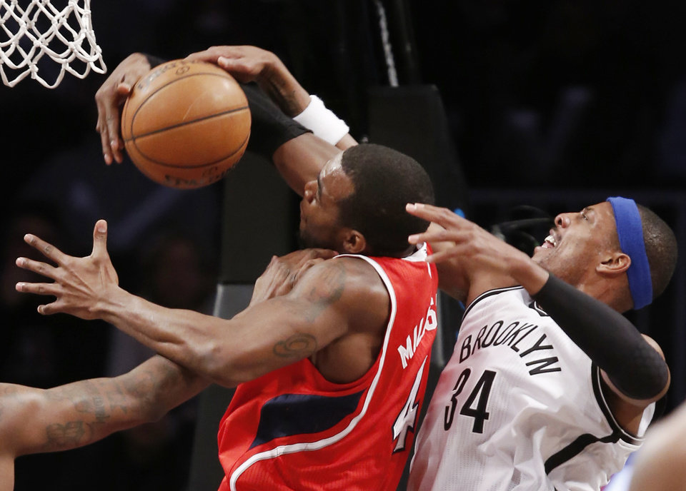 Photo - Brooklyn Nets forward Paul Pierce (34) defends Atlanta Hawks forward Paul Millsap (4) in the first half of their NBA basketball game at the Barclays Center, Monday, Jan. 6, 2014, in New York. (AP Photo/Kathy Willens)