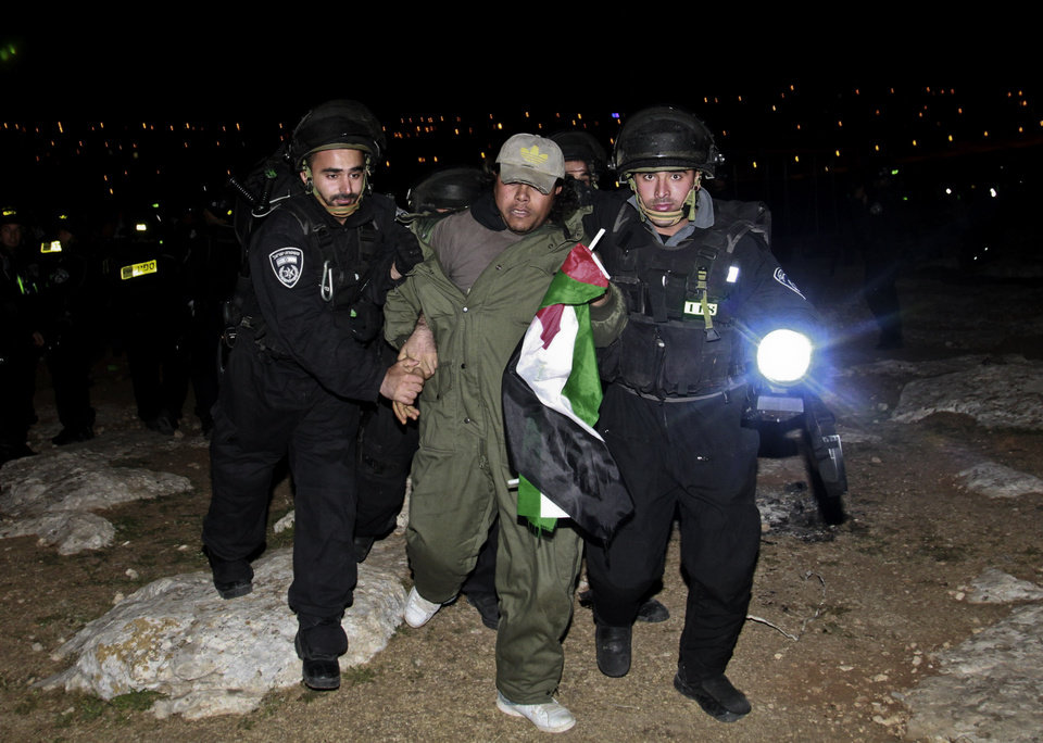 Photo - Israeli border policemen evict a Palestinian activist from an area known as E1 near Jerusalem, Sunday, March 24, 2013. Palestinian activists erected tents in the E1 area to protest Israeli plans for a new settlement in the area. (AP Photo/Nasser Shiyoukhi)