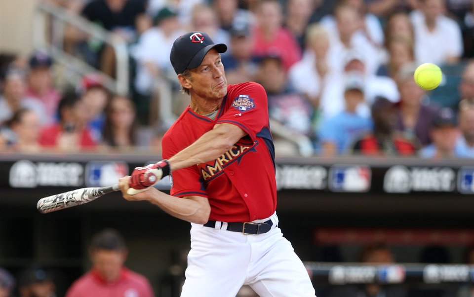 Photo - Actor James Denton bats during the All-Star Legends & Celebrity Softball Game, Sunday, July 13, 2014, in Minneapolis. (AP Photo/Jim Mone)