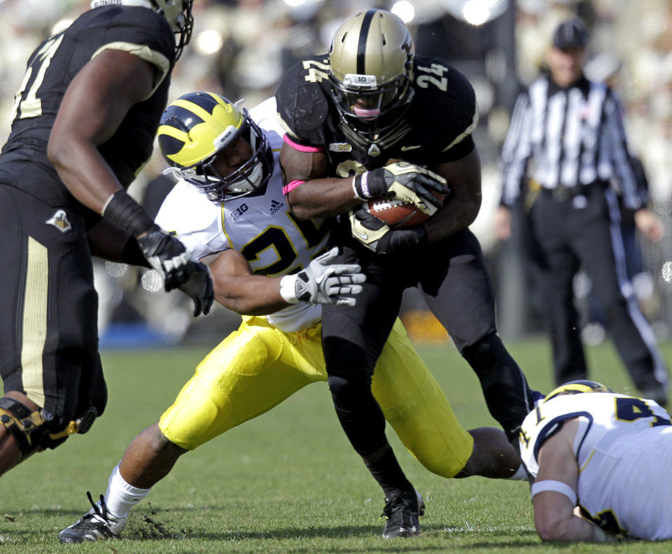Michigan linebacker Kenny Demens, left, tackles Purdue running back Akeem Shavers during the first half of an NCAA college football game in West Lafayette, Ind., Saturday, Oct. 6, 2012. (AP Photo/Michael Conroy)