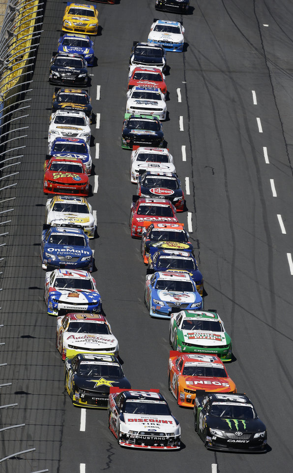 Photo - Kyle Busch, front right, and Brad Keselowski, left, lead the field as they approach the starting line to begin the NASCAR Nationwide series History 300 auto race at the Charlotte Motor Speedway in Concord, N.C., Saturday, May 24, 2014. Kyle Larson won the race. (AP Photo/Gerry Broome)