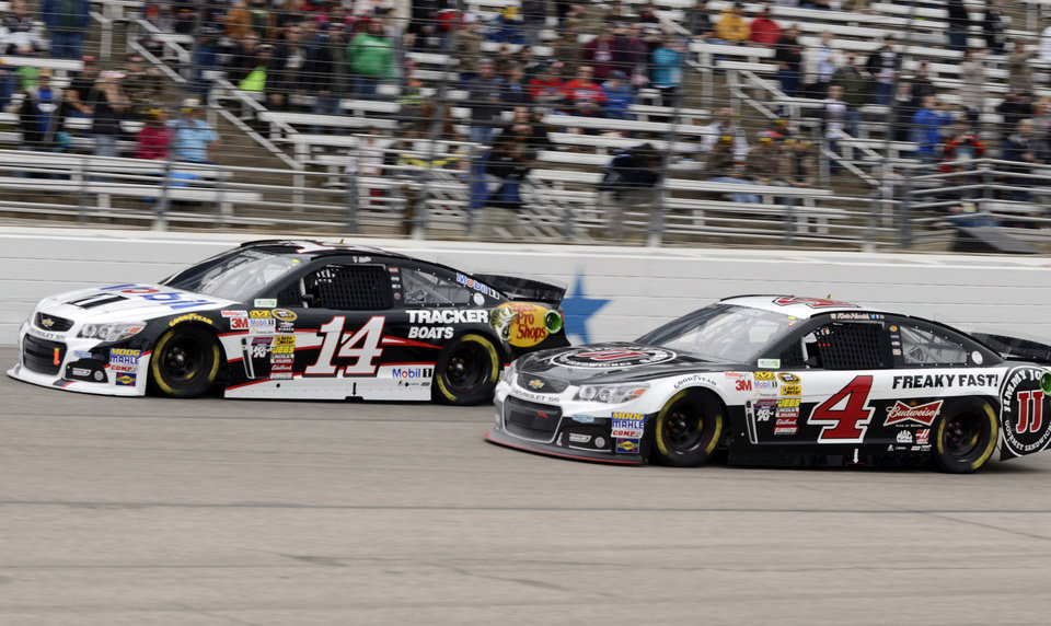 Photo - Tony Stewart (14) and Kevin Harvick (4) race through Turn 4 during the NASCAR Sprint Cup series auto race at Texas Motor Speedway, Monday, April 7, 2014, in Fort Worth, Texas. (AP Photo/Larry Papke)
