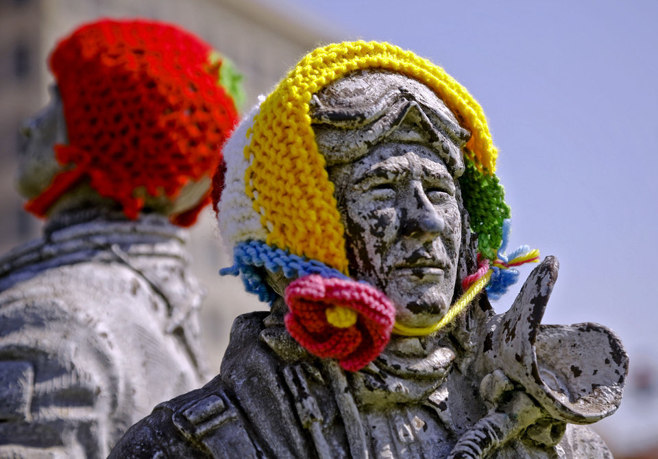 Photo - Knitted hats are attached to statues in the Enid town square on Friday. The public art project was established to bring the town together to display 'art graffiti' created from items made and donated by the community.  Photo by Chris Landsberger, The Oklahoman  CHRIS LANDSBERGER - CHRIS LANDSBERGER