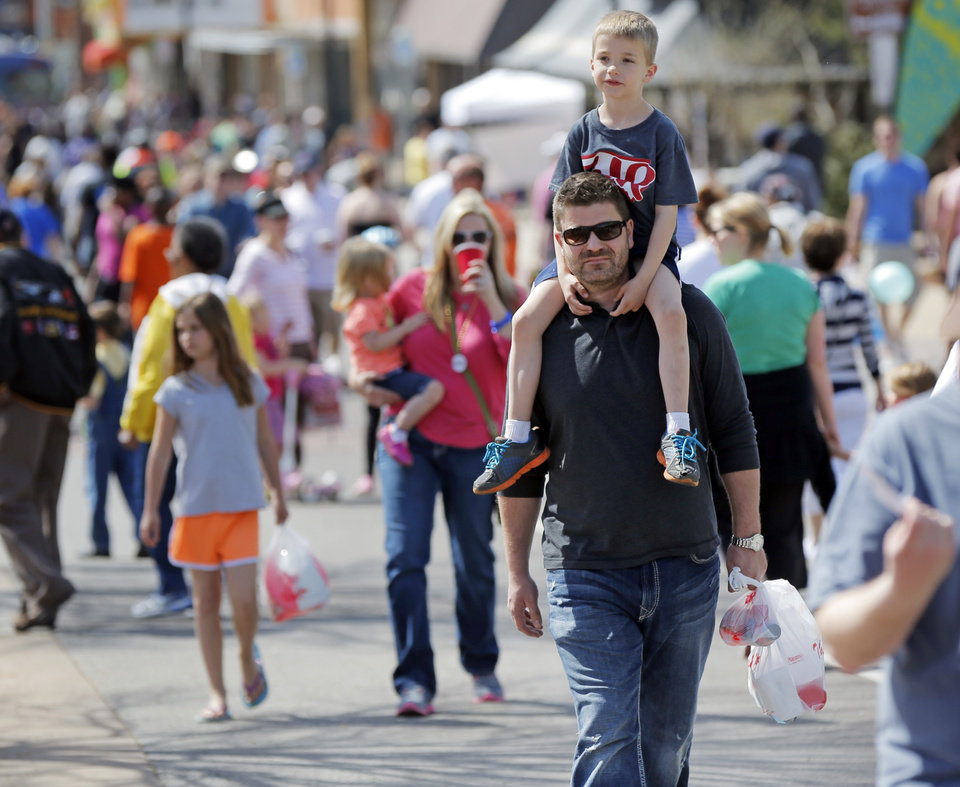 Photo -  Noah Giordano, then 6, sat on the shoulders of his father, Robert Giordano, during the Open Streets OKC event this past March along NW 23rd Street between Robinson and Western. [Photo by Doug Hoke, The Oklahoman]