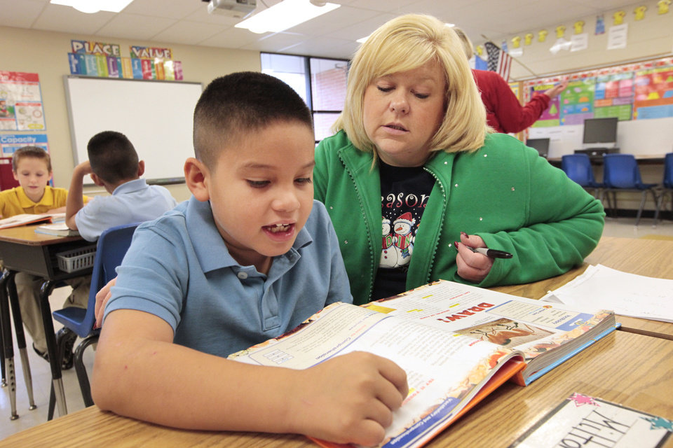 Photo - Pierce Elementary Principal Paula Pluess, right, helps third-grader Milton Celaya with a reading assignment, Wednesday, December, 4, 2013. Photo by David McDaniel, The Oklahoman